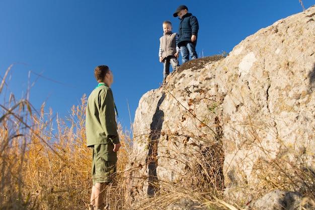 제복을 입은 백인 남성 스카우트가 지상에 서서 가을 기후의 큰 바위 위에서 어린 아이들과 이야기하고 있습니다.