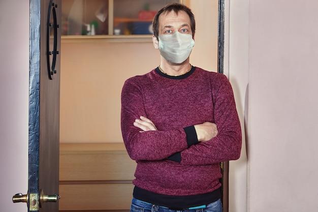 50 세 정도의 백인 남성이 집에서 격리하는 동안 코로나 19 유행 기간에 일회용 의료용 안면 마스크를 쓰고 아파트에 서 있습니다.