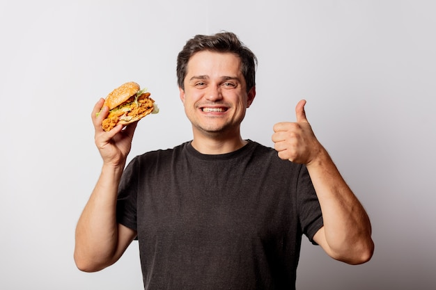 White man in black t-shirt with burger on white wall