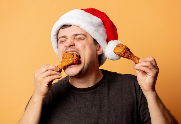White man in christmas hat with chicken drumsticks on white wall