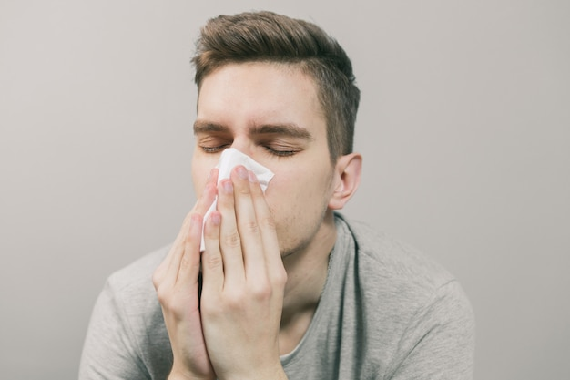 White man gets sick and blows his nose into a white napkin