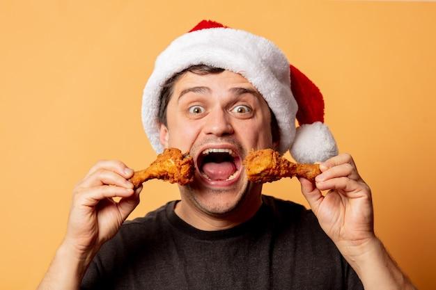 白い壁に鶏のモモ肉とクリスマスの帽子の白人男性