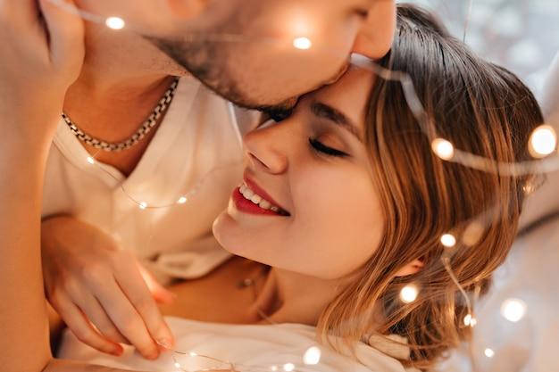 Uomo bianco che bacia fidanzata in fronte. ritratto del primo piano del marito amorevole che esprime tenerezza alla moglie.