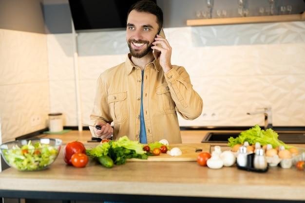 あごひげを生やした白人男性が笑顔でキッチンの電話で