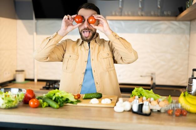 Белый мужчина с бородой улыбается и веселится на кухне.
