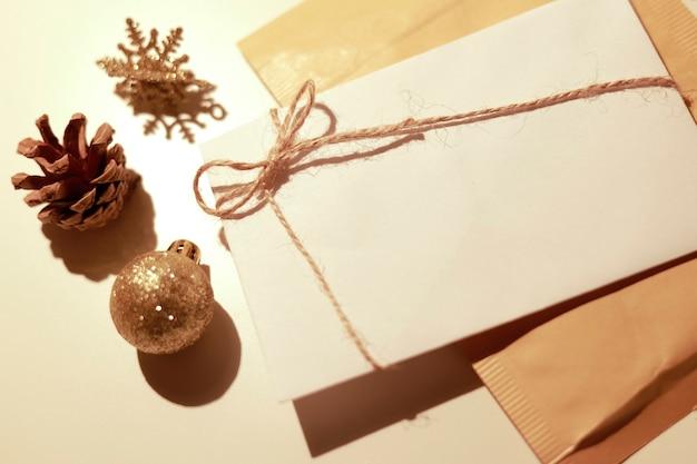 その周りに金のクリスマス飾りが付いた白いマニラ封筒
