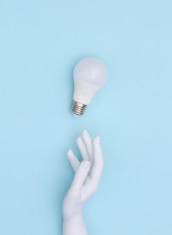 白いマネキンの手と青い背景のled電球。上面図