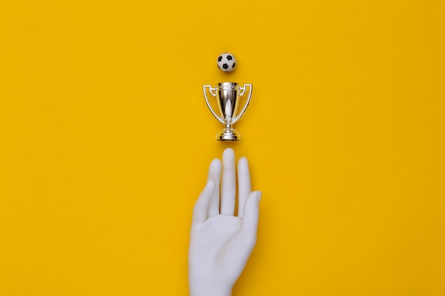 White mannequin hand, championship cup and sosser ball on a blue background. top view