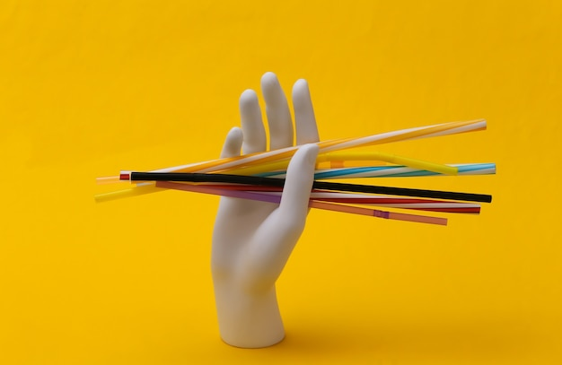 White mannequin hand holding many plastic cocktail tubes on yellow background