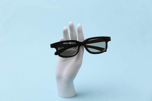 White mannequin hand holds 3d glasses on blue background