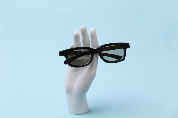 흰색 마네킹 손에는 파란색 배경에 3d 안경이 있습니다.