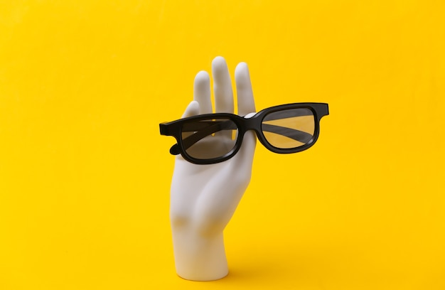 White mannequin hand holds 3d glasses on yellow background