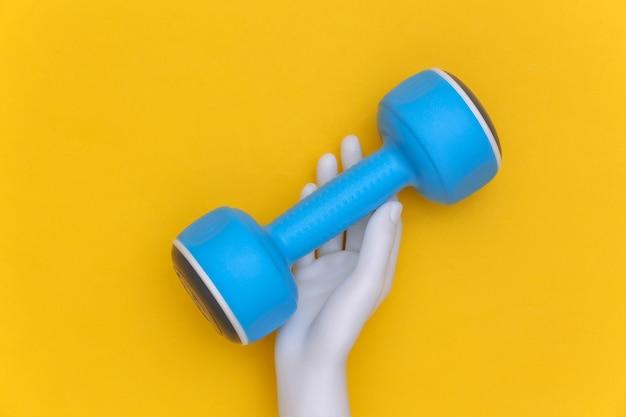 白いマネキンの手は黄色の背景に青いプラスチック製のダンベルを保持します。スポーツとフィットネスのコンセプト