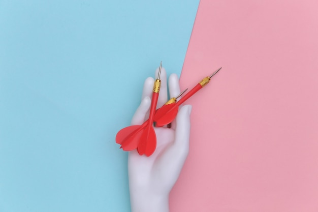 White mannequin hand holds dart needle on pink blue pastel background. top view