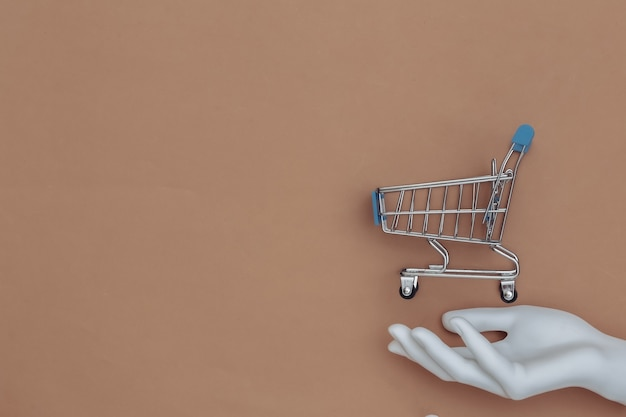 White mannequin hand holds a mini shopping cart on brown background. top view