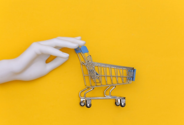 White mannequin hand holds a mini shopping cart on a yellow background. top view
