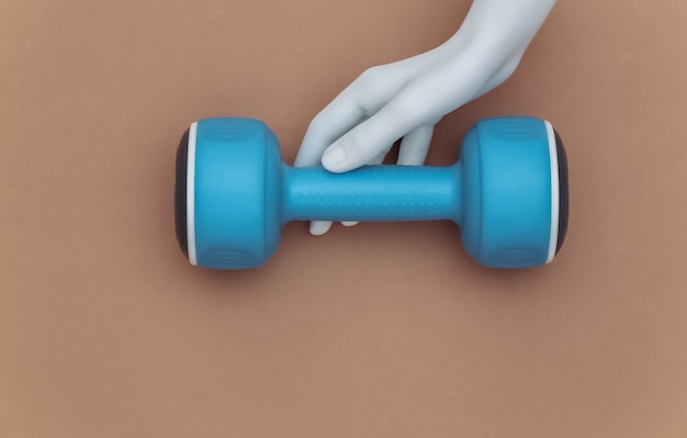 白いマネキンの手は茶色の背景にプラスチック製のダンベルを保持します。スポーツとフィットネスのコンセプト