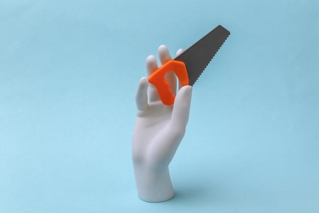 白いマネキンの手は青い背景におもちゃのこぎりを保持します。リノベーションコンセプト、業界。ミニマリズム