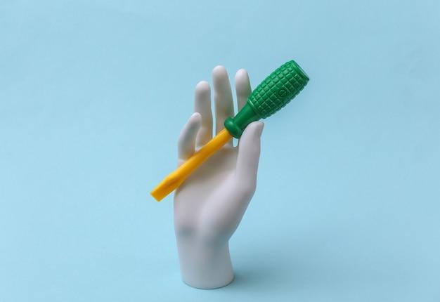 白いマネキンの手は青い背景におもちゃのドライバーを保持します。