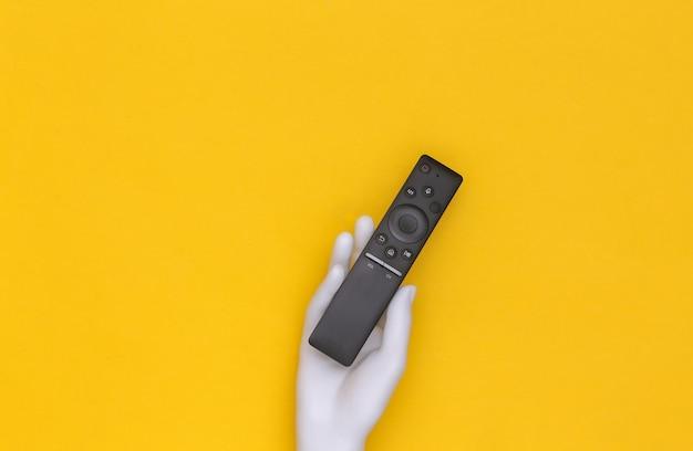 Белая рука манекена держит пульт от телевизора на желтом фоне. вид сверху