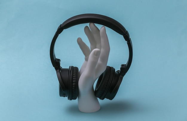 헤드폰을 끼고 있는 흰색 마네킹 손은 파란색 배경에 서 있습니다.