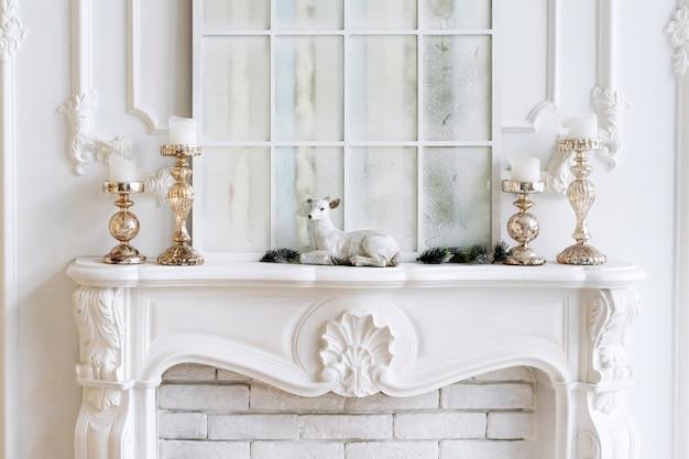 キャンドルとクリスマスの装飾が施された白いマントルピース。クラシックなインテリア。
