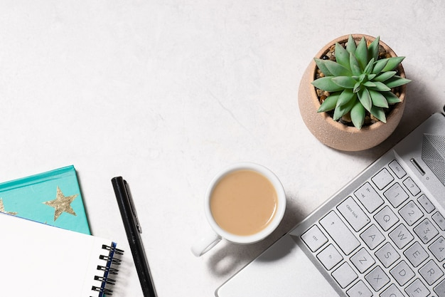 White marble office desktop with lap top, notebook, cup of coffee and succulent flower in a pot