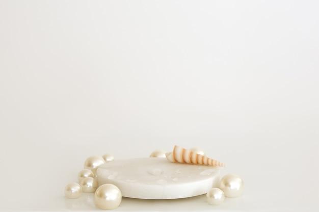 진주, 조개, 물이 있는 흰색 대리석 연단은 흰색 배경에 떨어집니다. 제품 연단, 화장품 프레젠테이션. 창의적인 모의. 미용 제품을 위한 받침대 또는 플랫폼.
