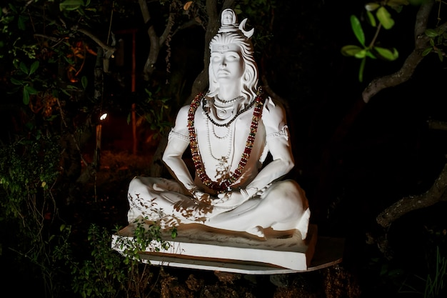 White marble statue of shiva with a garland of flowers around his neck. in the night park