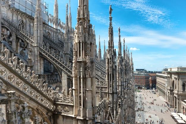 Белые мраморные статуи на крыше знаменитого собора дуомо ди милано на площади в милане, италия