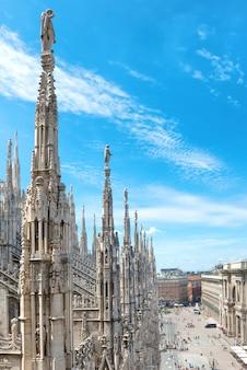 이탈리아 밀라노의 광장에 있는 유명한 두오모 디 밀라노 대성당의 지붕에 있는 흰색 대리석 조각상