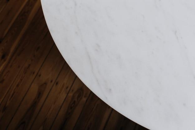 Tavolo in marmo bianco e pavimento in legno