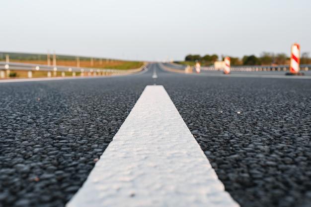 高速道路のアスファルト道路の白いマーキングラインがクローズアップ