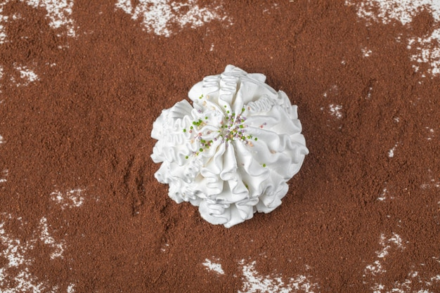 A white marshmallow on blended coffee powder.