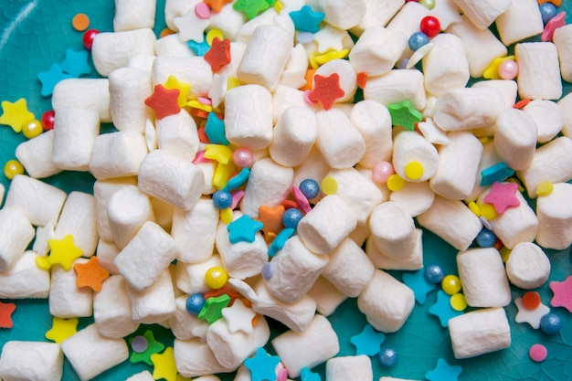 White marshmallow and colorful festive sprinkling on a blue plate. macro.
