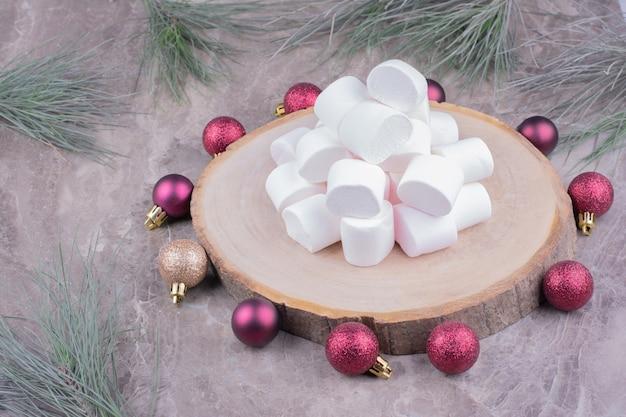 周りに赤いクリスマスボールと木製の大皿に白いマシュマロ