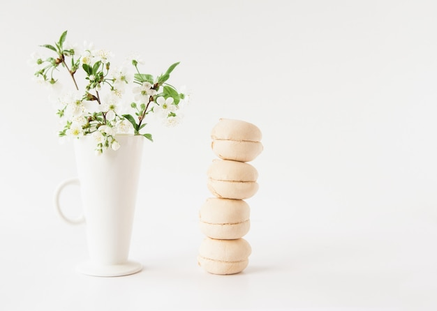 White marshmallows stack and white flowers in a white vase on white background