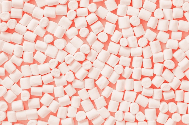 White marshmallows on trendy color pastel background. flat lay