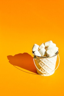 White marshmallows in a white metal bucket on a yellow background copy space, an ingredient for making a christmas drink and decorating cakes. junk unhealthy food. Premium Photo