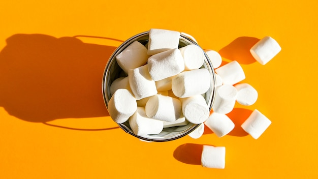 White marshmallows in a white metal bucket on a yellow background copy space, an ingredient for making a christmas drink and decorating cakes. junk unhealthy food.