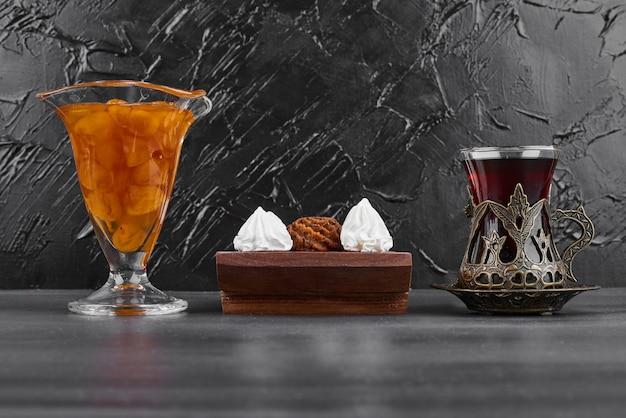 チョコレートプラリネとお茶のグラスと白いマシュマロ。
