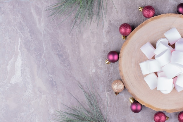 White marshmallows on a wooden platter with red christmas balls around