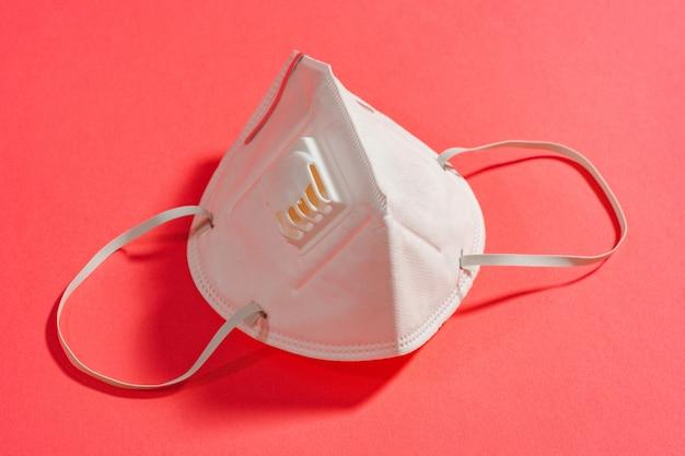 코로나 바이러스 전염병 2021 동안 균일 한 분홍색 배경에 밸브가있는 흰색 마스크