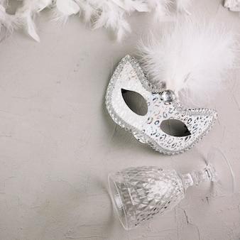 Белая маскарадная маска из перьев карнавала с бокалом и пером боа на бетонном фоне