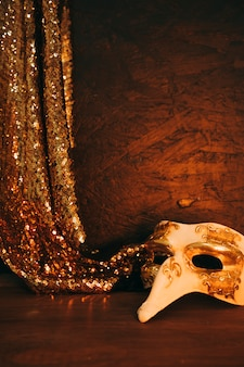 White masquerade mask with hanging golden sequins fabric against textured background
