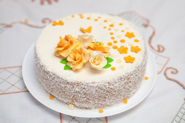 White mastic cake decorated with flowers, closeup