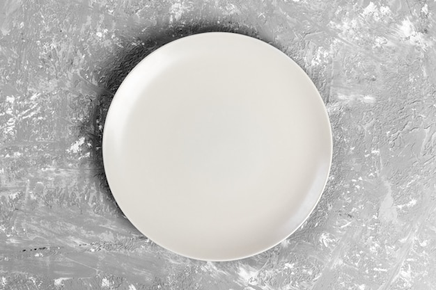 White matte round dish on the of a gray rextured table