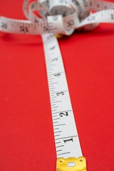 赤い背景に白い巻尺。長さと円周の測定。体重を減らして太ります。