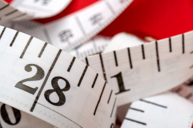빨간색 배경에 흰색 측정 테이프입니다. 길이와 둘레 측정. 살을 빼고 살찌세요.