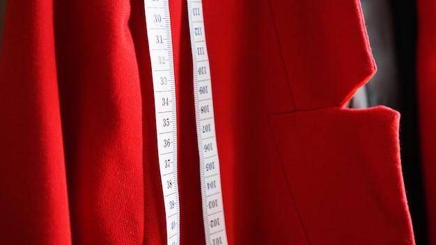 재킷의 빨간색 천 배경에 흰색 측정 테이프. 재봉 옷 개념